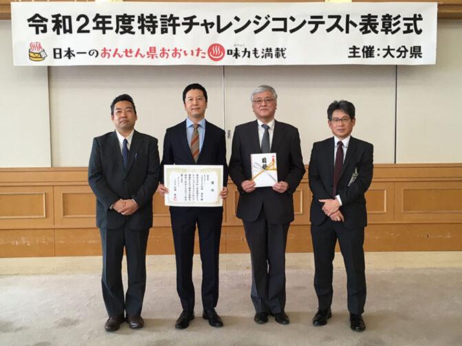 特許チャレンジコンテストの横断幕の前に整列する男性4名。左から2番目で賞状を掲げるのが石井社長、その右隣で賞金の目録を掲げるのが首藤テクニカルセンター長